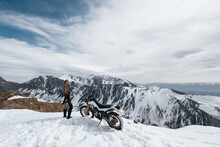 Woman Motorcyclist Standing Near Her Enduro Motorcycle On Snowy Mountain Top, Snow Peaks Skyline View, High Beautiful Mountains