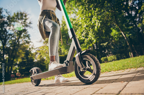 Fototapeta Cropped view of her she teenage teen trendy skinny slim fit hipster girl's legs riding kick scooter spending free time sunny day having fun activity sport in forest wood outdoor youth hobby obraz