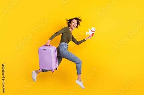 Full size profile side photo of crazy girl jump run fast with luggage plane visa isolated on shine yellow color background