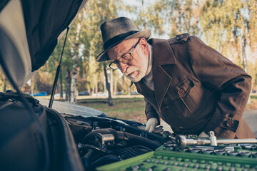 Photo of retired old man look motor examination problem automobile fixing wear brown coat cap eyewear outside