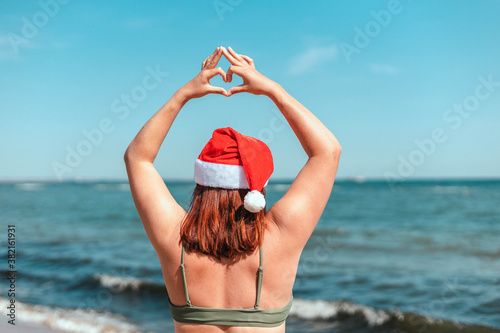 Fotografie, Obraz Happy girl in santa hat and swimsuit showing heart gesture with hands while stan