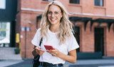 Half length portrait of cheerful caucasian female in trendy wear spending time on street using smartphone, beautiful millennial hipster girl blogger looking at camera in town holding mobile phone