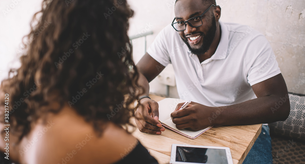 Fototapeta Successful male student in classic eyeglasses for vision correction enjoying live conversation with intelligent female,dark skinned man and woman have brainstorming meeting for cooperation on planning