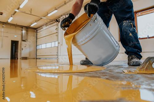 Fototapeta Worker applying a yellow epoxy resin bucket on floor.