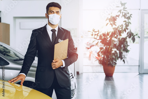 Fototapeta Man car dealer wearing protective medical mask on his working place