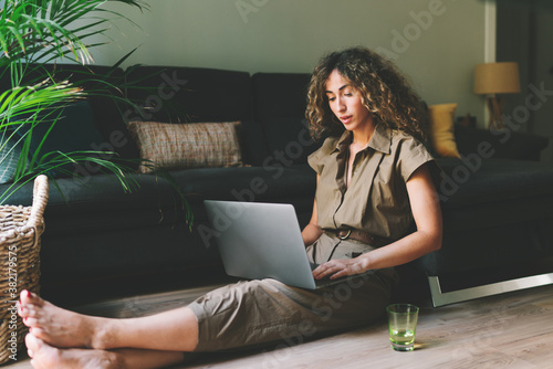 Fényképezés Beautiful female in casual outfit chilling on a floor beside comfortable couch in a living room with laptop on her knees