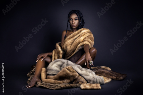 Fotografie, Obraz A portrait of a serene young black female with long dreadlocks, beautiful makeup and perfect lips sitting by herself on fur in a studio with dark background wearing jewelry & a fur coat