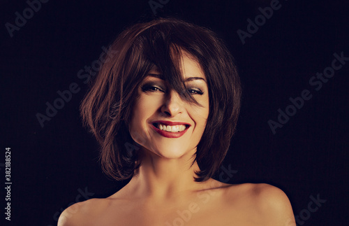 Foto Beautiful happy laughing bright makeup woman shaking her black short hair on black background