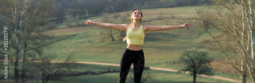 Obraz A young slim athletic girl in sportswear performs a set of exercises. Fitness and healthy lifestyle  against the background of green spring pasture hills. - fototapety do salonu