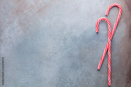 Fotografiet Christmas candy cane lied on blue background