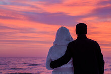 Man In Black Warm Overcoat Hugging Woman In White Fur Coat. Young Couple Standing And Staring At Small Waves Of Sea And Colorful Sunset Light In Sky. Peaceful Atmosphere In Winter Evening. Back View.