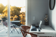An Interior Of A Cozy Room With A Desktop And A Laptop On It With A USB Hub And Wireless Graphic Tablet Near On The Table; A Glass Door Leads To A Small Balcony With A Beautiful Sunny View And A Table