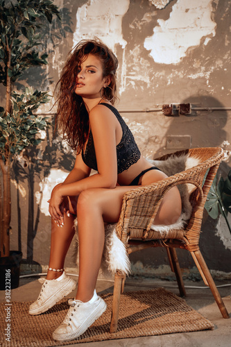 Obraz Pensive cute woman posing sitting on chair around some decorations in warm place in sunset. - fototapety do salonu