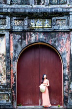 A Young Vietnamese Woman In A Traditional Ao Dai Dress And Hat Standing At The Gateway To The Imperial Purple City, Hue, Vietnam