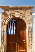 A Greek Flag Hangs Under The Stone Archway In The Doorway Of One Of The Captain's Houses Of Lindos On Rhodes, Dodecanese, Greek Islands, Greece