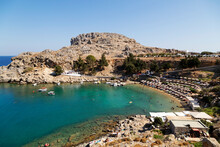 Sun Shades Line The Beach At St. Paul's Bay On A Sunny Day In Lindos On Rhodes, Dodecanese, Greek Islands, Greece