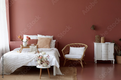 Cozy bedroom interior of retro armchair, vintage chest dwarf and bed on the back Wallpaper Mural