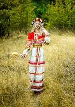A Young Girl In A Red Folk Costume Walks On The Grass In The Park, Holding Spikelets In Her Hands.