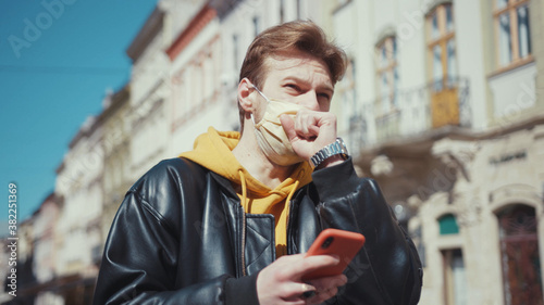 Cuadros en Lienzo Blonde stylish caucasian guy wearing medical mask using smartphone coughing badly covering face suffering symptoms of coronavirus outdoors