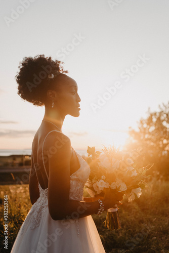 A beautiful young black bride and groom posing for portraits in a meadow on their wedding day - 382253364