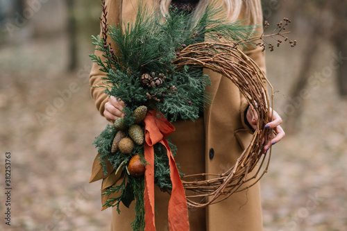 Hands of unrecognisable person holding a Christmas wreath, Christmas decoration