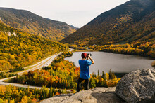 Young Photographer Focusing On Landscape Of New Hampshire Fall Foliage