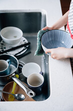 Cute Girl Washing Dishes In Kitchen