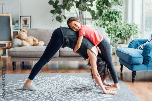 Chinese mother and daughter doing yoga at home