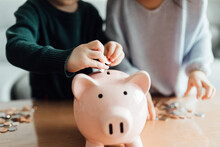 Family Saving Money In A Piggy...