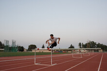Young Sportsman Hurdling In Evening