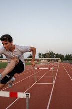 Sportsman Jumping Over Hurdle With Effort