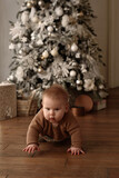 Baby crawling in a room decorated for Christmas