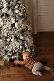 6-month old baby playing with decoration of Christmas tree