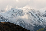 Wind blowing snow over mountain peaks
