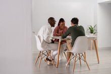 Cheerful Multiracial Colleagues Sitting At Table In Office