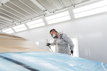 Technician Painting Car With C...