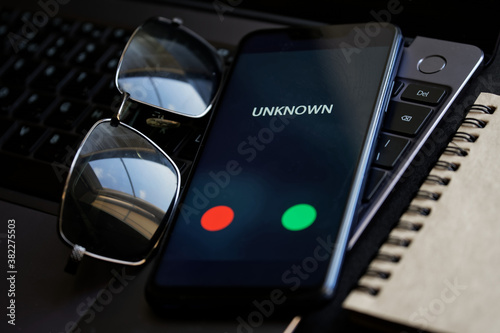 Fototapeta A black smartphone with an unidentified call lies on the laptop keyboard next to sunglasses and a notepad. The problem of hacking, espionage and the darknet. Protection of personal information obraz