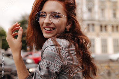 Fototapety, obrazy: Cool girl in plaid outfit and eyeglasses smiling