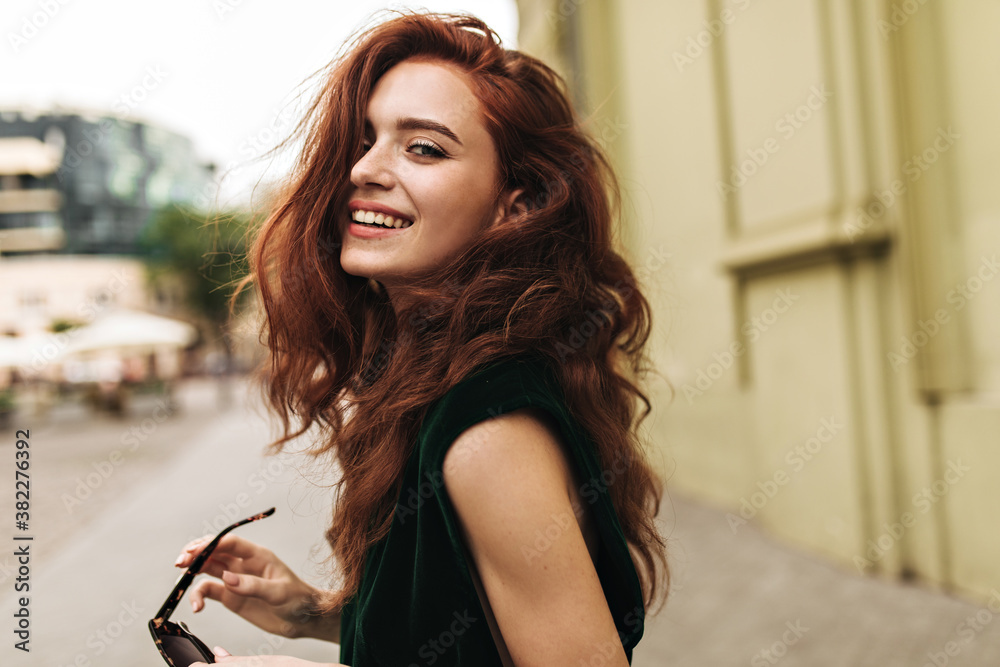 Fototapeta Attractive woman in dark green outfit smiling outside
