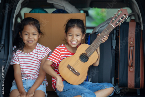 Fotografie, Obraz Happy asian child girl playing guitar and singing a song with her sister in a car trunk in family trip