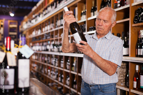 Fotografie, Obraz Portrait of senior man visiting winehouse in search of bottle of good wine