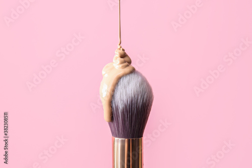 Fototapeta Brush with foundation for makeup on color background