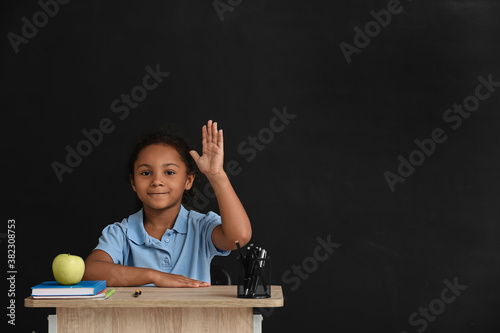 Little African-American pupil sitting at school desk against dark background Fototapete