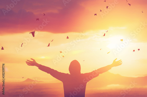 Obraz Freedom feel good and travel adventure concept. Copy space of silhouette man rising hands on sunset sky at top of mountain and bird fly abstract background. - fototapety do salonu