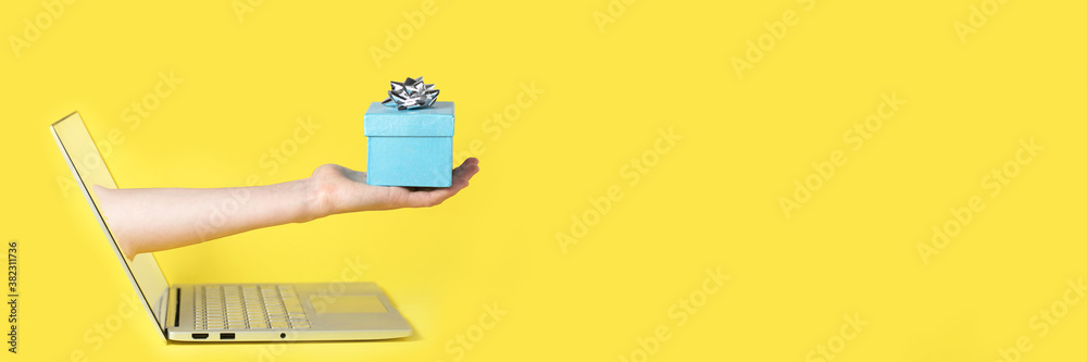 Fototapeta Giving a gift from the screen of the computer online yellow background and blue present with the silver bow on the top of it
