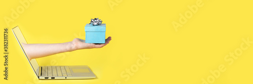 Giving a gift from the screen of the computer online yellow background and blue present with the silver bow on the top of it