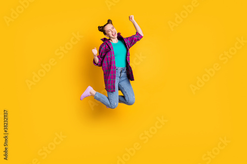 Full length photo of attractive crazy excited teen lady jump up air support sports team raise fists scream goal cheering wear casual plaid shirt shoes jeans isolated yellow color background