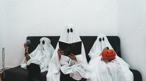 Fotografie, Obraz Trio of halloween ghosts sitting in the sofa reading, drinking wine and playing