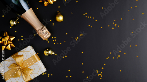 Fototapeta Christmas composition. Flat lay champagne bottle, gift box, xmas decorations, tinsel, golden confetti on black background. Christmas greeting card, festive banner mockup obraz
