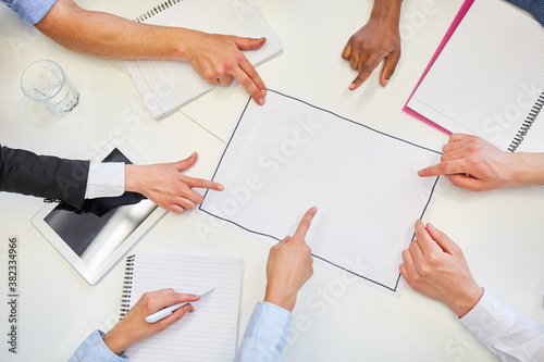 Hands pointing to plan at business strategy meeting